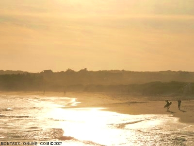 Surfers walking down the beach in the afternoon at Ditch Plains in Montauk